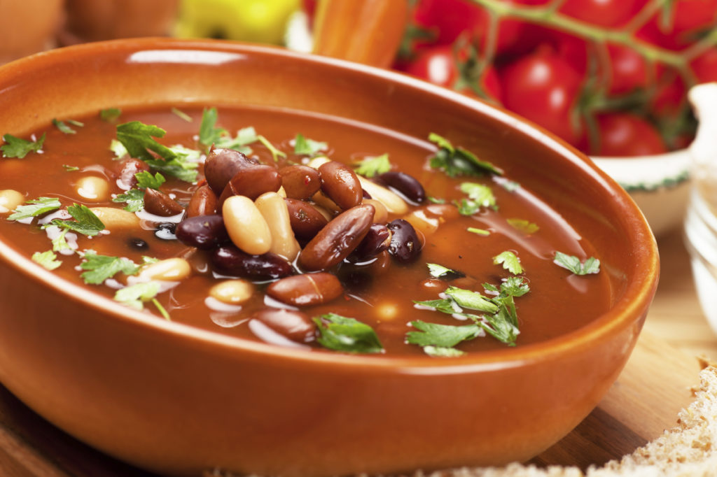 Thick kidney bean soup in rustic bowl, selective focus image